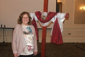 Pastor Sherrie Hadden standing next to a Cross