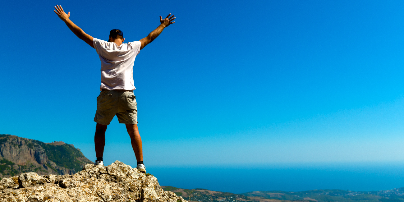 man standing on top of mountain with hands outstretched