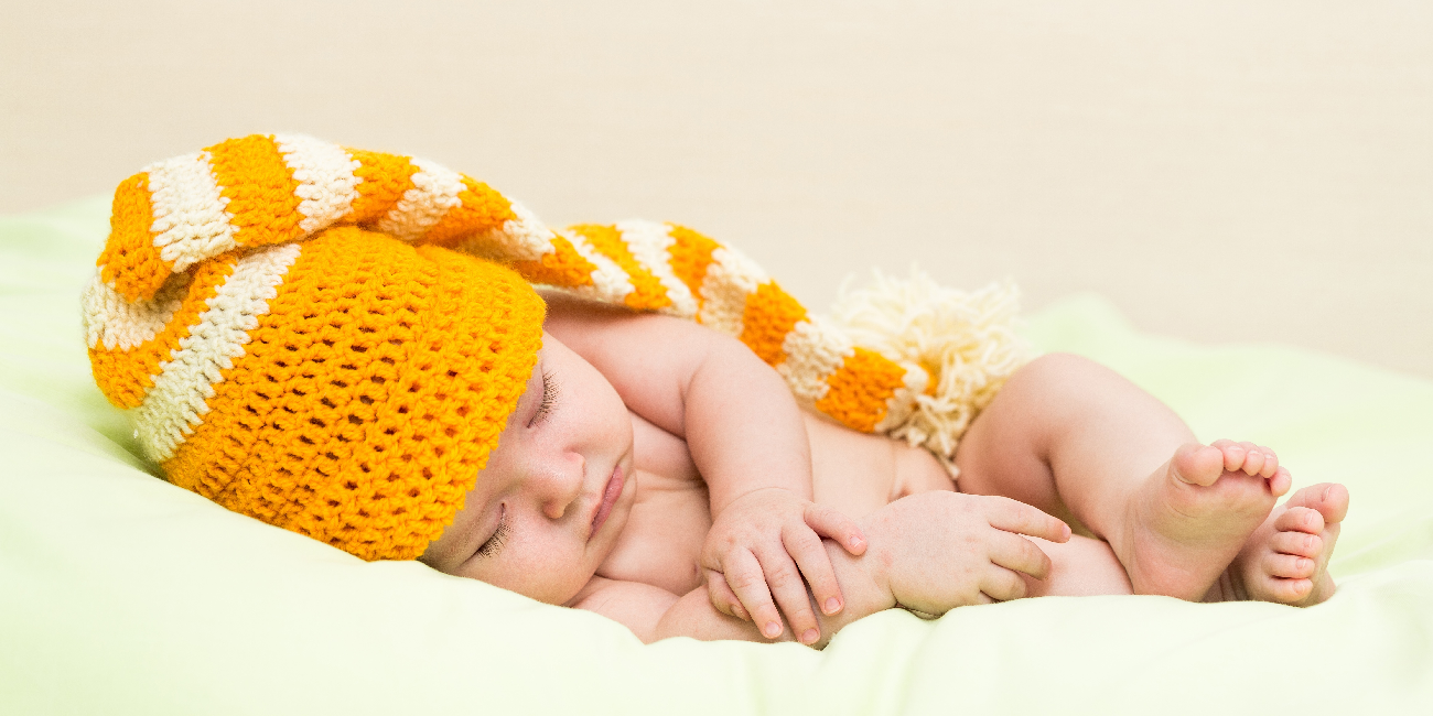 baby lying asleep on a cushion, wearing a knitted hat