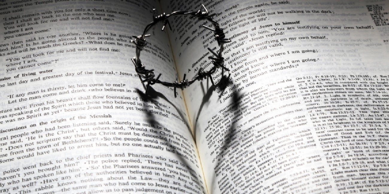 barbed-wire crown with heart shadow on an open bible